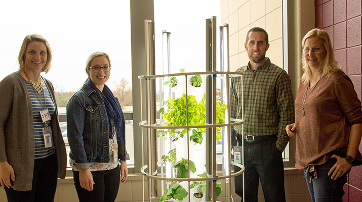 Four teachers standing around a tower garden at Fort Riley Middle School.