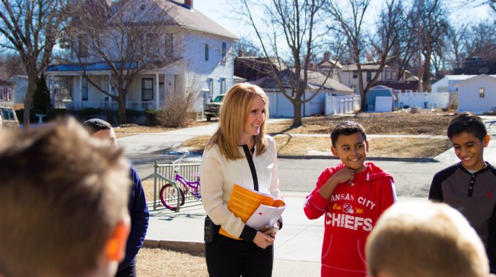Principal Amy Roether speaking with students outside.