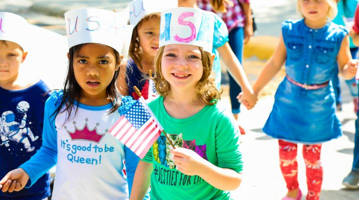 Photo of children walking in a Freedom Walk wearing USA hats.