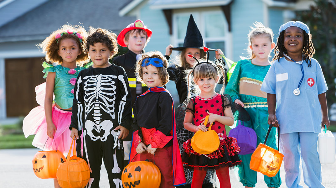 Children dressed in costume for Halloween trick or treating.